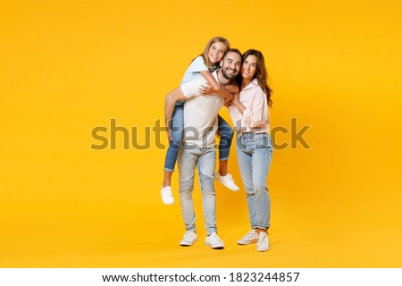 Full length portrait of smiling funny young parents mom dad with child kid daughter teen girl in t-shirts giving piggyback ride to joyful sit on back isolated on yellow background. Family day concept