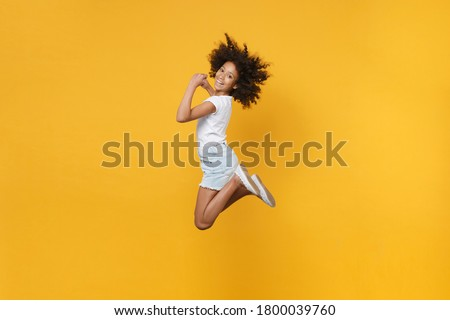 Full length portrait of smiling little african american kid girl 12-13 years old in white t-shirt isolated on yellow wall background studio portrait. Childhood lifestyle concept. Jumping, having fun Сток-фото ©