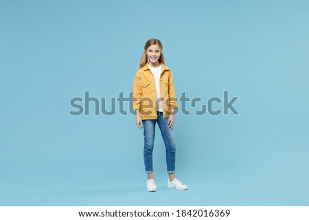 Full length portrait of smiling little blonde kid girl 12-13 years old in yellow jacket posing isolated on blue wall background studio. Childhood lifestyle concept. Mock up copy space. Looking camera Stock photo ©