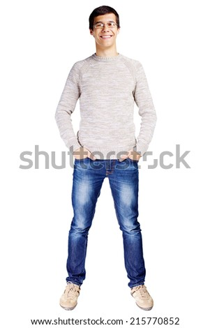 Full length portrait of smiling young man in glasses and beige sweater with hands in his jeans pockets isolated on white background