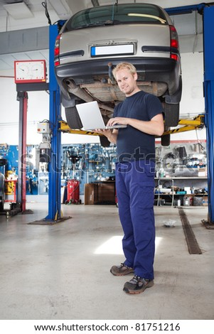Full length portrait of smiling young mechanic using laptop in his auto repair shop