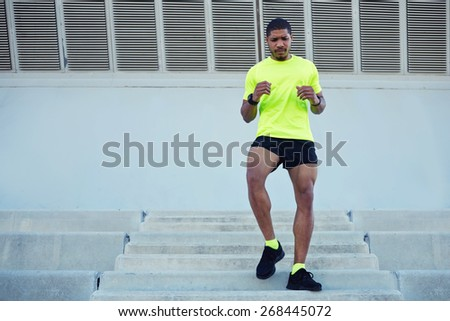 Full length portrait of sporty young man running down a flight of stairs while training outdoors at sunny afternoon,male runner dressed in bright t-shirt working out outdoors while doing legs exercise stock photo