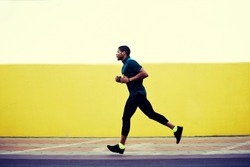 Full length portrait of strong male jogger with muscular body running fast against bright copy space background for your text message or content, pumped man working out while jogging outdoors in city