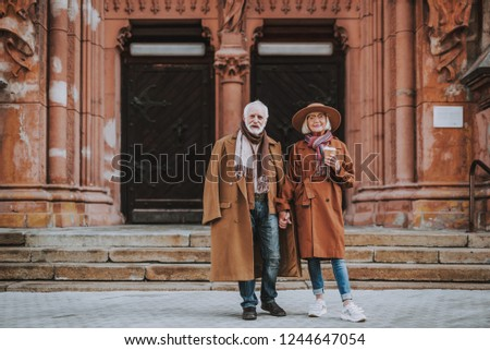 Full length portrait of stylish bearded man and his wife standing near old building. Lady in hat holding cup of coffee