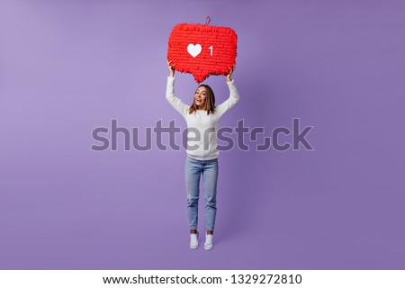 Full-length portrait of stylish female blogger standing on purple background. Dreamy caucasian girl in white sweater dancing in studio. #1329272810