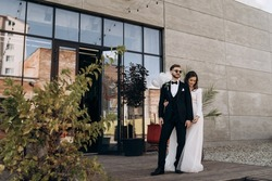 Full-length portrait of stylish newly married European couple. The bride in white dress and veil is hugging the groom. Groom with a beard and sunglasses dressed in a classic black suit.