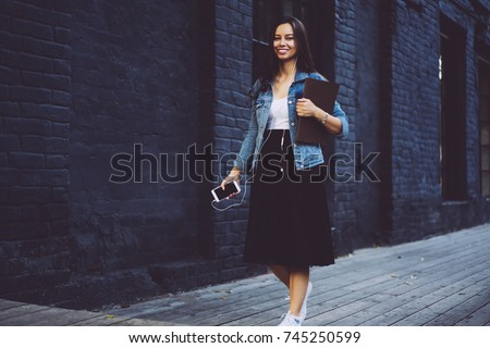 Full length portrait of stylish student with training books in hands looking at camera with smile and listening music in earphones connected to modern smartphone.Promotional background for text #745250599