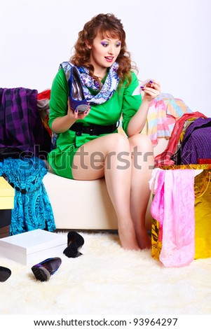 full-length portrait of surprised young shopaholic woman sitting on sofa with purchases and looking at check