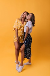 Full-length portrait of tanned girls in casual outfit. Winsome female friends standing on orange background.