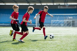 Full length portrait of three boys wearing red uniform running across football field during junior team practice, copy space