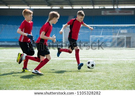 Full length portrait of three boys wearing red uniform running across football field during junior team practice, copy space #1105328282