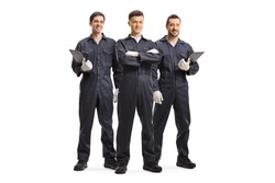 Full length portrait of three mechanic workers in uniforms isolated on white background