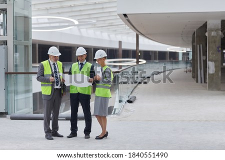 Full length portrait of three successful business people wearing hardhats and inspecting plans while standing at construction site indoors, copy space Stock foto ©