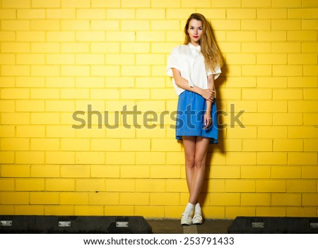 Shutterstock Full Length Portrait of Trendy Hipster Girl Standing at the Yellow Brick Wall Background. Urban Fashion Concept. Copy Space.