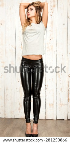 Full Length Portrait of Trendy Hipster Girl Standing at white Wall Background.Urban Fashion Concept.Copy Space,elegant leggings.street fashion patent leather punk print legging black,matte patent