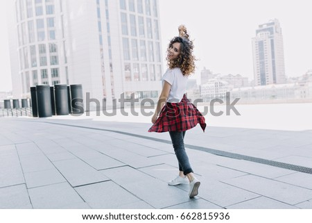 Full-length portrait of trendy stylish girl in the city. She walks on the street and turn around on camera. Dressed in white t-shirt and white sneakers. Truly emotions. Place for text.