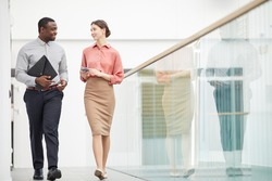 Full length portrait of two contemporary business people walking towards camera and talking in minimal office building interior, copy space