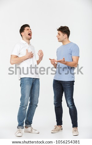 Full length portrait of two handsome young men talking and laughing isolated over white background