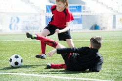 Full length portrait of unrecognizable teenage boy falling on grass after being attacked by another player on football field during junior team practice