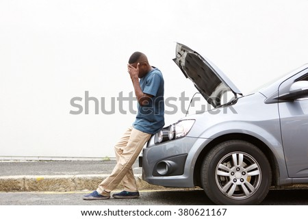 Full length portrait of upset young african man standing in front of a broken down car parked on the side of a road