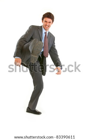 Full length portrait of very angry young businessman hard  kicking  isolated on white