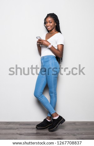 1f4660b39a Full length portrait of woman with afro hairstyle wearing t-shirt and jeans  using smartphone