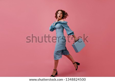 Full-length portrait of worried tourist with suitcase. Emotional brunette lady in long dress running with valise.