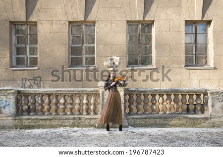 Full length portrait of Young adult sexy woman with long hair playing on broken violin on old retro fence and wall with windows in the Gothic style of classicism archtect backdrop
