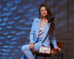 Full length portrait of young beautiful elegant woman wearing blue costume and sitting at high chair in dark interior with colorful light. Fashioable stylish business woman