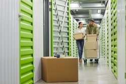 Full length portrait of young couple holding cardboard boxes walking towards camera in self storage unit, copy space
