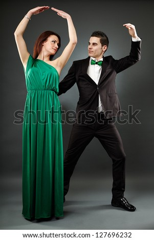 Full length portrait of young elegant tango dancers over gray background
