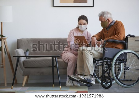 Full length portrait of young female nurse assisting senior man in wheelchair using digital tablet at retirement home, both wearing masks, copy space Foto stock ©
