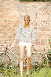 Full length portrait of young girl standing with bicycle in front of wall