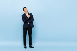 Full length portrait of young handsome southeast Asian businessman looking up and pointing to copy space on light blue studio background