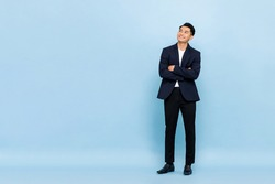 Full length portrait of young handsome southeast Asian businessman with arms crossed looking up to copy space on light blue studio background