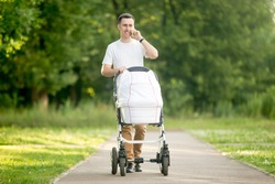 Full length portrait of young happy father dressed in white T-shirt walking in park and pushing carriage with newborn baby, talking on phone, smiling happily