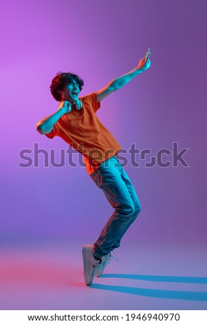 Full-length portrait of young man in casual clothes dancing isolated on gradient pink-purple background in neon light. Concept of human emotions, facial expression, youth culture. Copy space for ad. Foto stock ©