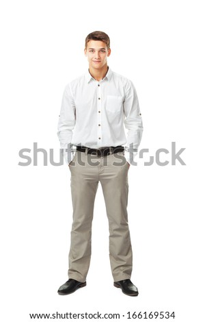 Full length portrait of young man wearing white shirt and light trousers with hands in pockets isolated on white background