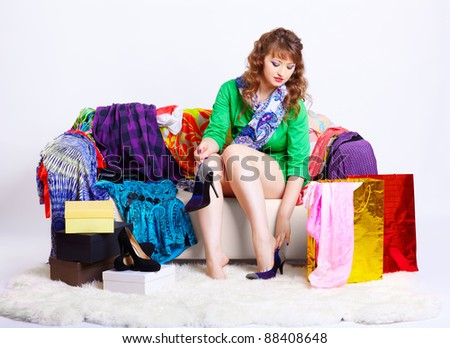 full-length portrait of young shopaholic woman relaxing her tired legs on sofa among clothes, court shoes boxes and shopping bags