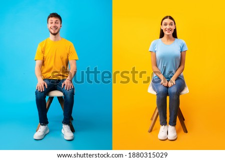 Full length portrait of young smiling positive man and woman sitting on two chairs and looking at camera, isolated over blue and yellow halved background wall, studio shot. Seated couple resting Stockfoto ©
