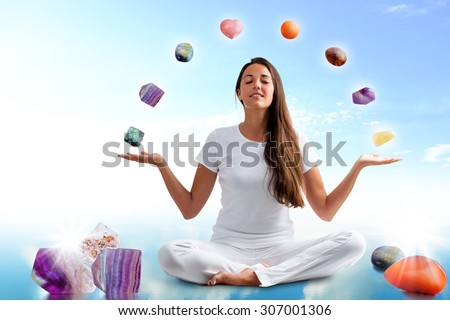Full length portrait of young woman dressed in white doing yoga with precious gemstones.Conceptual image with colorful gemstones floating around girl.
