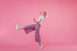 Full-length portrait of young woman in trendy pants dancing in studio with happy smile. Indoor shot of slim stylish girl in pink wig having fun.