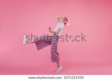 Full-length portrait of young woman in trendy pants dancing in studio with happy smile. Indoor shot of slim stylish girl in pink wig having fun.