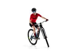 Full-length portrait of young woman, professional bicyclist with road bike, cycle isolated over white background.. Concept of sport, acton, motion, speed, race, healthy lifestyle. Copy space for ad.