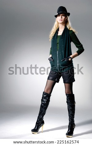full-length portrait of young woman wearing boots with hat standing in studio
