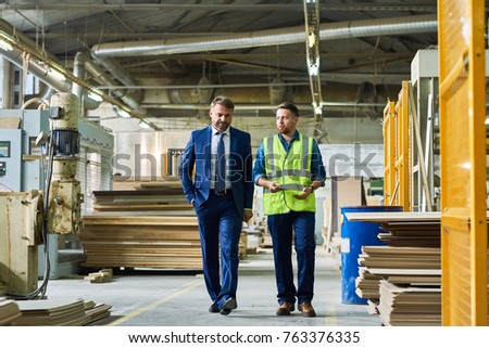 Full length portrait of young workman giving tour of modern factory to handsome mature businessman discussing possible investment, copy space