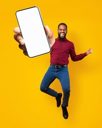Full length portrait on joyful black man jumping, gesturing YES and showing cellphone with empty space for mobile app on white screen, orange studio background. Creative collage