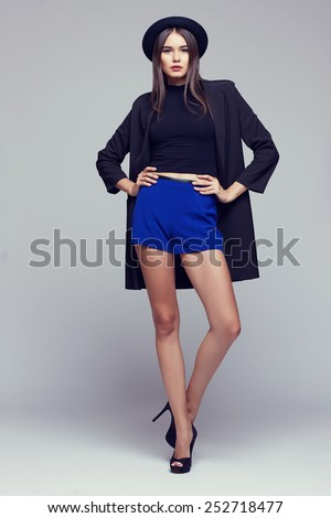 Full-length portrait young elegant woman in blue shorts, black jacket and hat. Fashion studio shot