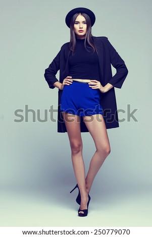 Full-length portrait young elegant woman in blue shorts, black jacket. Fashion studio shot