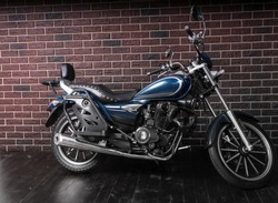 Full Length Profile of Blue Standard Cruiser Style Motorcycle in front of Brick Wall